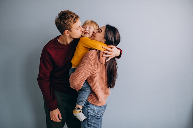 Young family with little son together on grey Free Photo