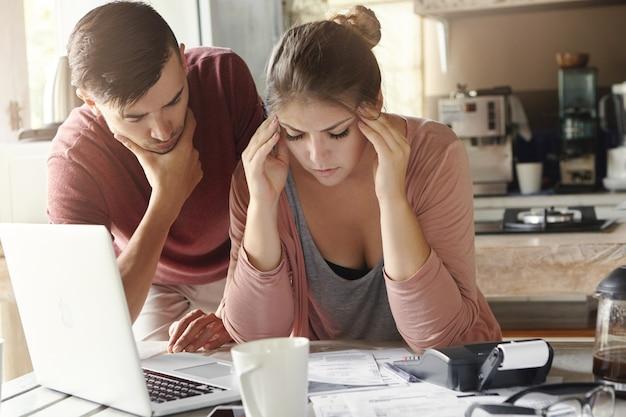 Giovane famiglia con molti debiti che affrontano lo stress finanziario Foto Gratuite