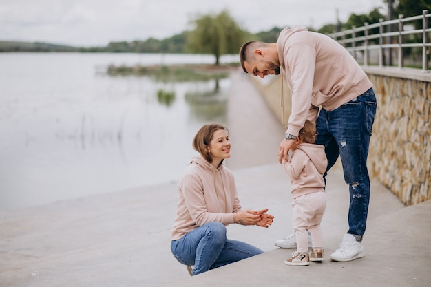 Young family with their little baby child in park by the lake Free Photo