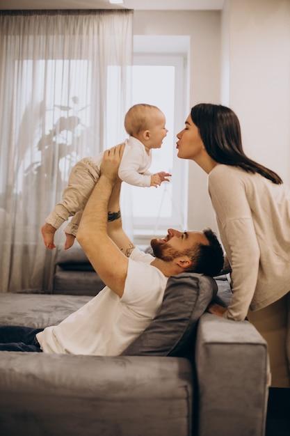 Giovane famiglia con la figlia del bambino del bambino che si siede sull'allenatore a casa Foto Gratuite