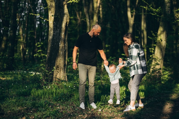 Young fanily with little daughter in the forest Free Photo