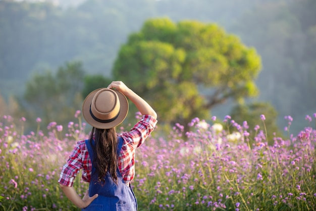 The young farmer admires the flowers in the garden. Free Photo