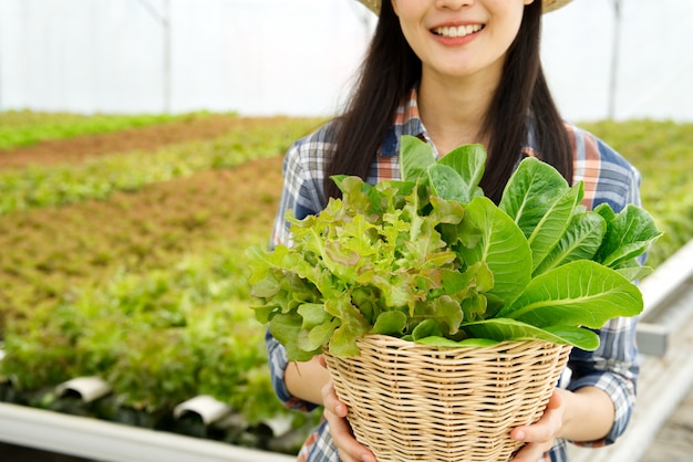 Young farmer girl holding basket of vegetables in hydroponic farm with smile Premium Photo