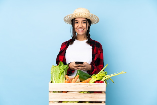 Young farmer woman holding fresh vegetables in a wooden basket sending a message with the mobile Premium Photo