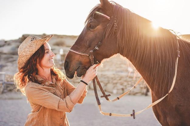 Молодая женщина фермера играя с ее бездарной лошадью в солнечном дне внутри ранчо загона Premium Фотографии