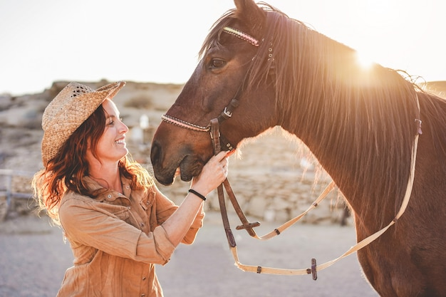 Young farmer woman playing with her bitless horse in a sunny day inside corral ranch Premium Photo