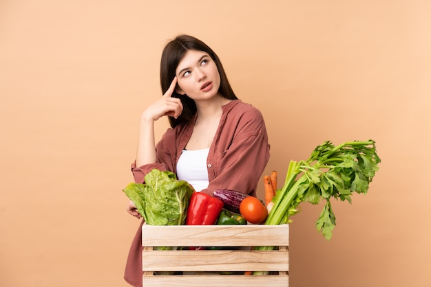 Young farmer woman with freshly picked vegetables in a box having doubts and thinking Premium Photo