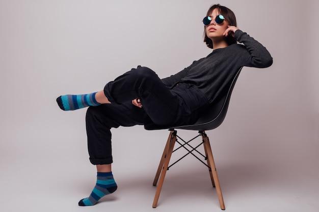 Giovane bella donna di modo in occhiali da sole che si siedono sulla sedia isolata Foto Gratuite