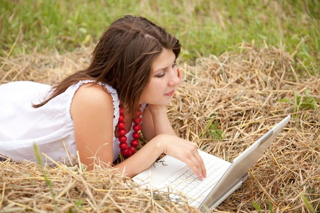 Young  fashion girl with notebook lying at field Premium Photo
