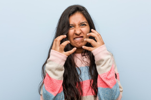 Young fashion indian woman upset screaming with tense hands. Premium Photo