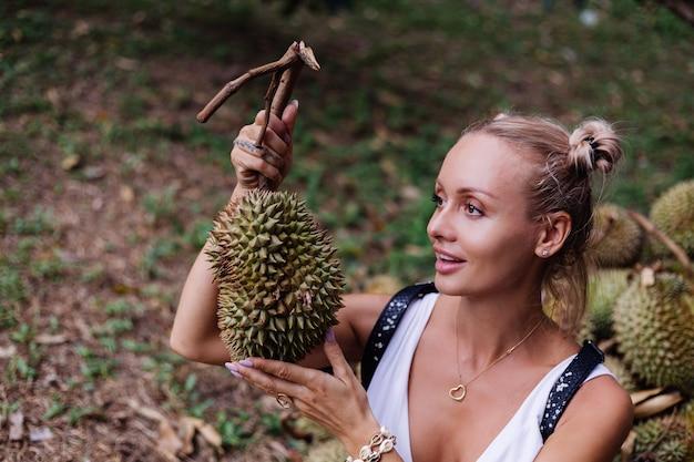 ドリアンの果物と熱帯のフィールドで若いファッションの女性 無料写真