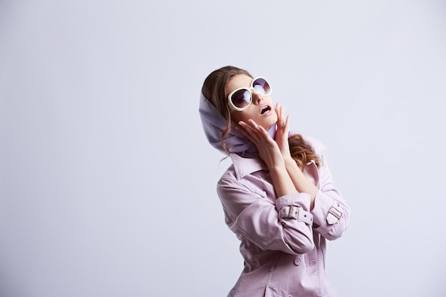 Young fashion woman posing in studio wearing pink coat and white sunglasses Premium Photo