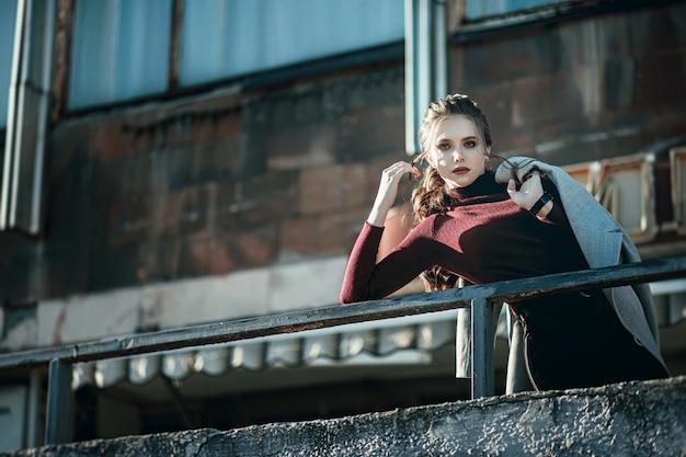 Молодая модная красивая женщина в черных джинсах и с темно-красной сумкой Premium Фотографии