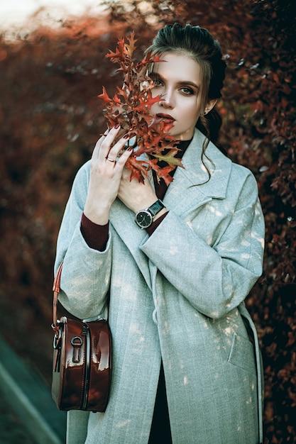 Молодая модная красивая женщина в длинном сером пальто, черных джинсах и с темно-красной сумкой. профессиональная модель. Premium Фотографии