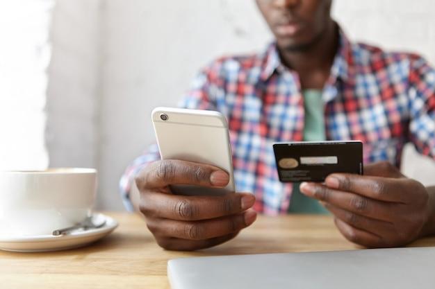 スマートフォンとラップトップのカフェに座っている若いおしゃれな男 無料写真