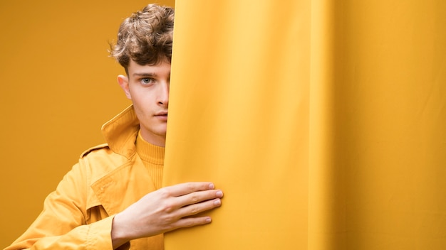 Young fashionable man behind curtain Free Photo