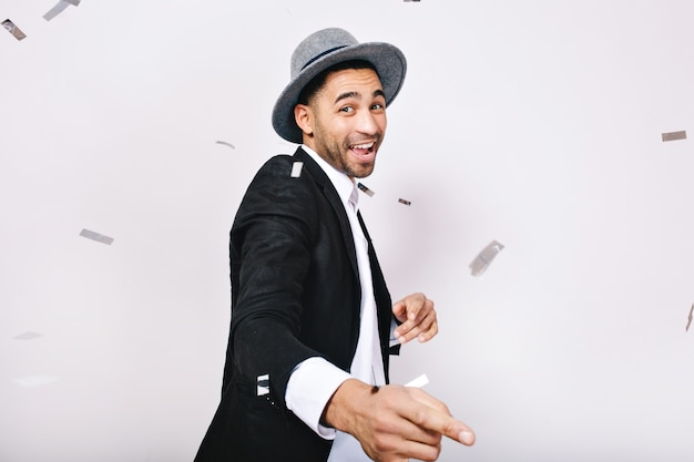 スーツ、帽子楽しんで、分離された見掛け倒しで踊るファッショナブルな若者。お祝い、パーティーの時間、ポジティブさを表現すること、楽しむこと、レジャー、幸福。 無料写真