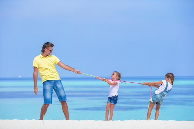 Young father and little girls have fun together during tropical vacation Premium Photo