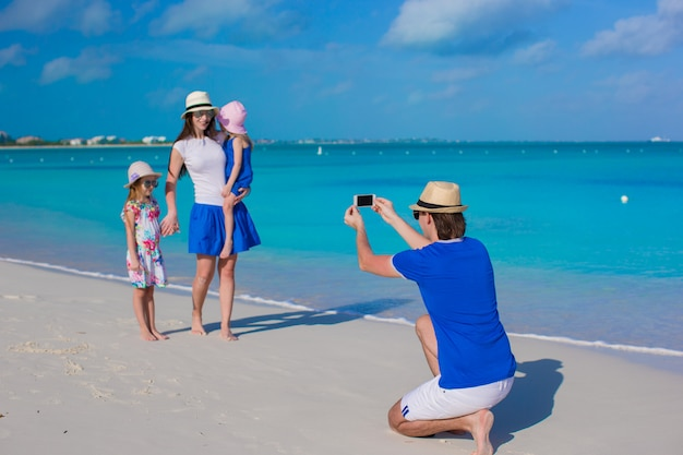 Young father making photo on phone of his family at the beach Premium Photo