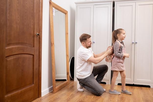 복도에서 학교에 가기 전에 그녀가 물건을 포장하는 것을 돕는 동안 그의 귀여운 작은 딸의 뒤에 작은 배낭을 넣어 젊은 아버지 프리미엄 사진