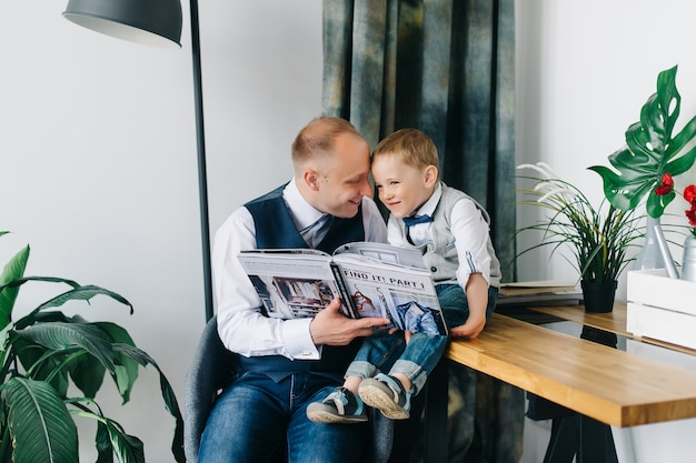 Молодой отец читает книгу, в то время как его прекрасный сын с помощью планшетного устройства, сидя на диване дома Premium Фотографии
