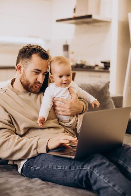 그의 딸과 함께 앉아서 집에서 컴퓨터를 사용하는 젊은 아버지 무료 사진