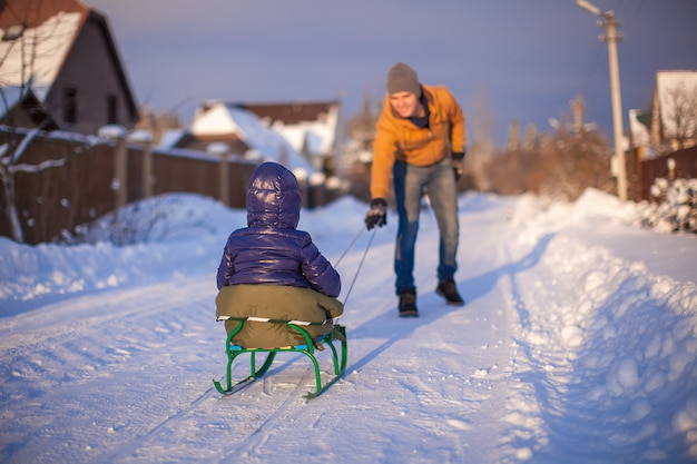 Young father sledding his little daughter on a sled in the snow outdoors Premium Photo