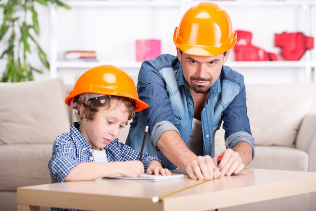 Young father teaches his little son tinkering. Premium Photo