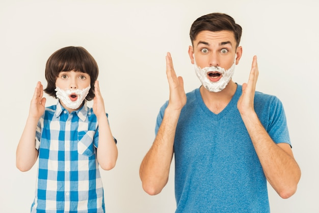 Young father teaches little son to shave at home. Premium Photo