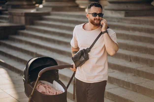 若い父親がベビーカーで赤ちゃんと一緒に外に出る 無料写真