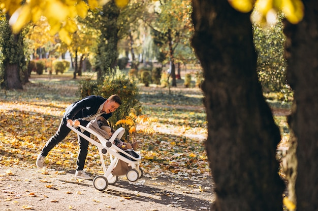 Young father walking with baby daughter in carriage in park Free Photo