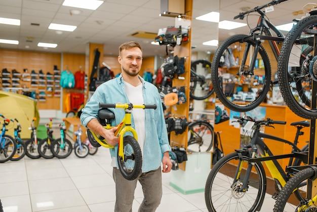 Молодой отец с детским велосипедом, покупки в спортивном магазине. Premium Фотографии