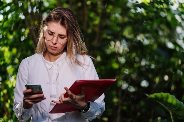 Молодая женщина сельскохозяйственный инженер звонит в теплице Бесплатные Фотографии