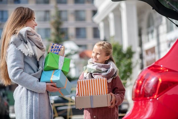 자동차 트렁크 근처 선물 상자를 들고 젊은 여성 및 십 대 소녀 프리미엄 사진