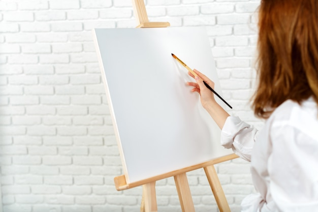 Young female artist painting picture in studio Premium Photo