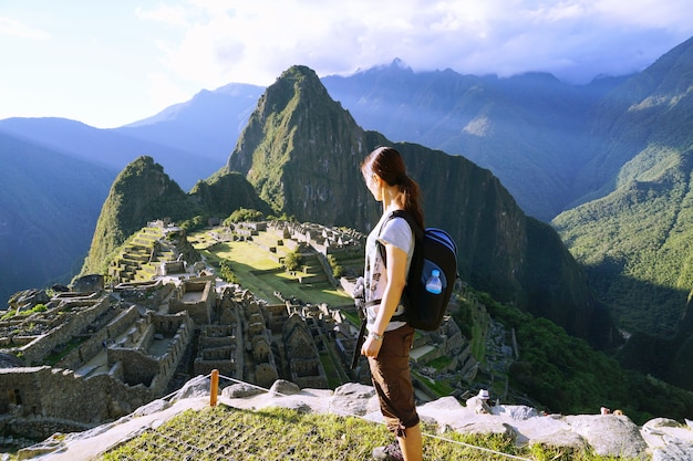 The young female asian solo traveller standing at the cliff looking at machu picchu, peru. Premium Photo