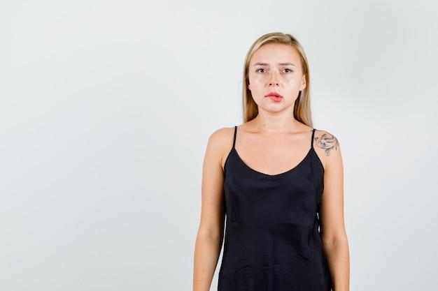 黒のサンドレスで唇を噛み、真剣に見える若い女性。 無料写真