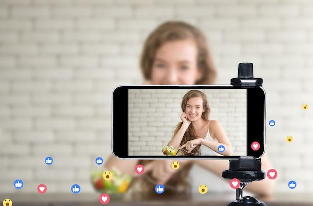 若い女性のブロガーとvlogger、オンラインインフルエンサーがスマートフォンを使用してソーシャルメディアで料理番組をライブストリーミング Premium写真
