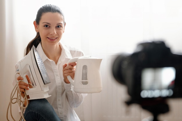 カメラのデジタル一眼レフヴロギングと若い女性ブロガーはボトルで家庭用品を現代のオンライン作業の概念 Premium写真