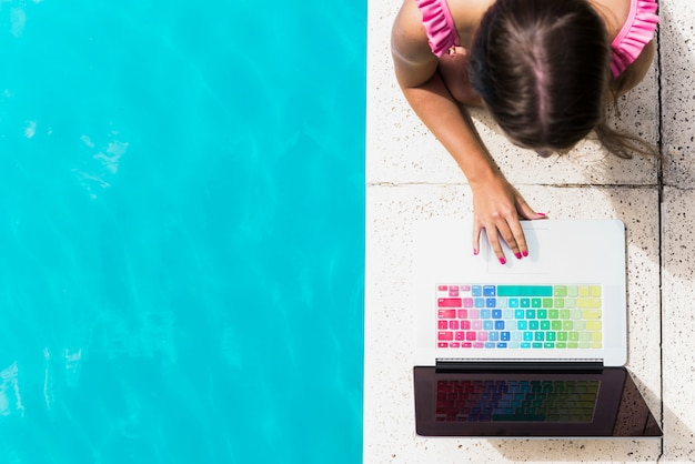 Young female browsing laptop on edge of pool Free Photo