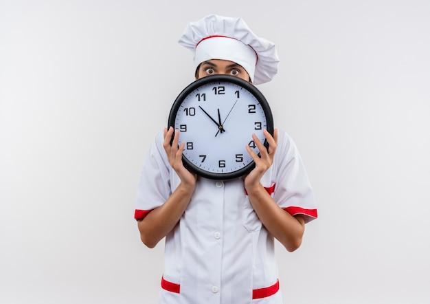 Giovane cuoco femmina che indossa uniforme da chef coperto faccia con orologio da parete sul muro bianco isolato con spazio di copia Foto Gratuite