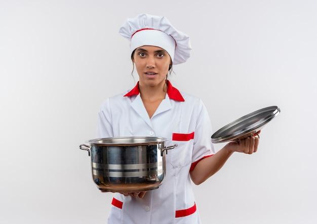 コピースペースと隔離された白い壁に鍋と蓋を保持しているシェフの制服を着た若い女性料理人 無料写真