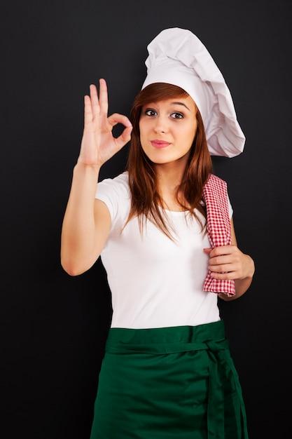 Giovane cuoco unico femminile di cottura che mostra segno giusto Foto Gratuite
