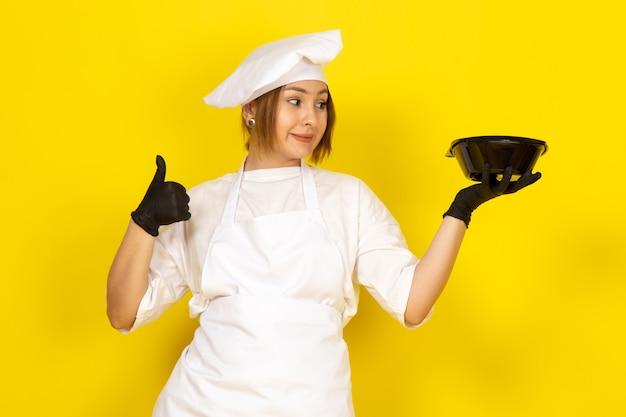 若い女性が白いクックスーツと黒いボウルを示す黒い手袋で白い帽子で調理 無料写真