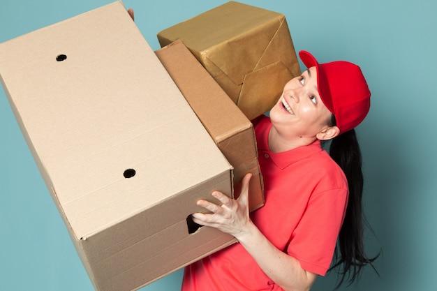青い壁にボックスを保持しているピンクのtシャツの赤い帽子の若い女性の宅配便 無料写真