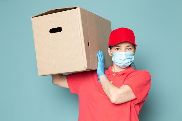 Young female courier in pink t-shirt red cap blue sterile mask holding box on the blue wall Free Photo
