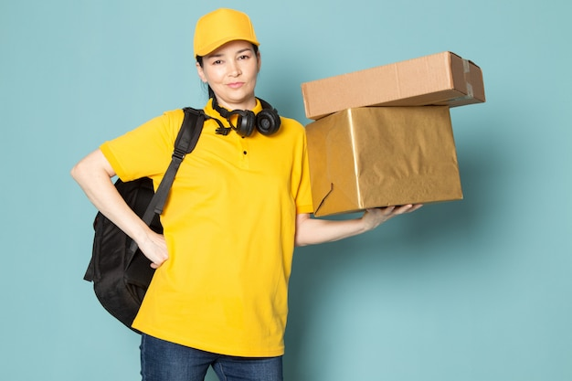 Young female courier in yellow t-shirt yellow cap holding box on the blue wall Free Photo