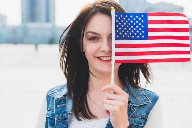 Young female covering face with american flag Free Photo