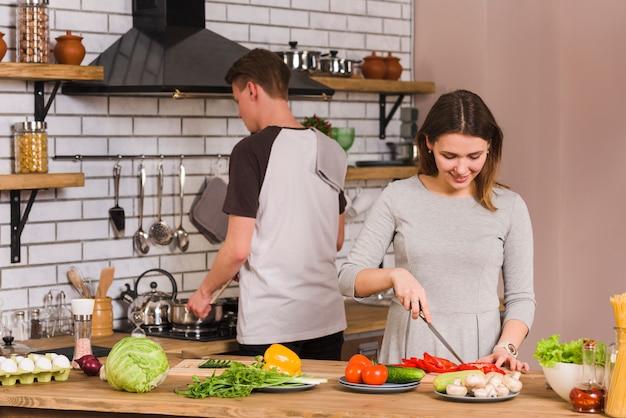 Young female cutting vegetables near boyfriend Free Photo