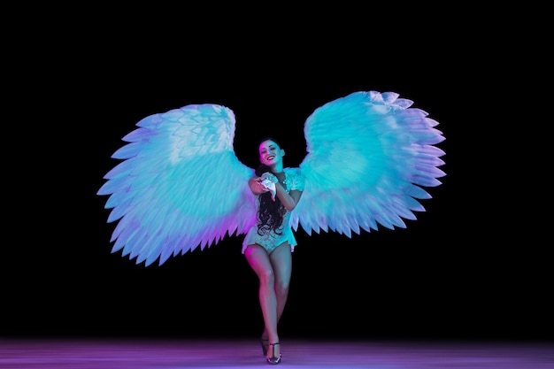 Young female dancer with angel's wings in neon light on black wall Free Photo